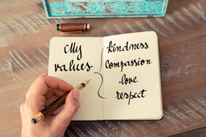 hand holding pen, writing in book: my values: kindness, compassion, love, respect